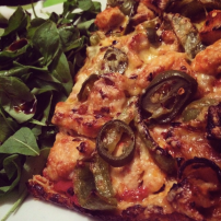 Pizza made with a cauliflower base and spinach on the side